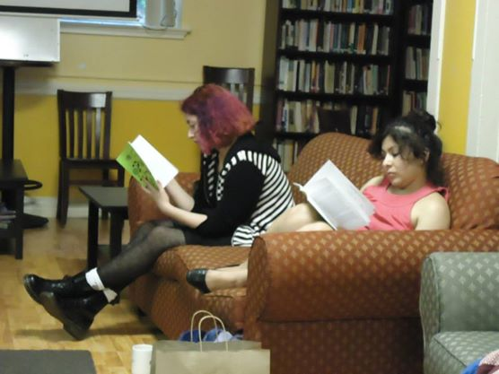 Attendees read the latest WOC Zine Collective at the potluck/networking party.
